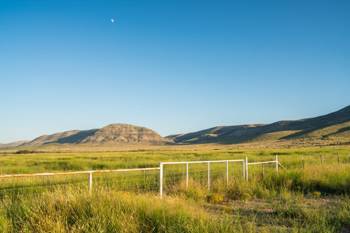 Photo of Red Mill Ranch, ranch gate in grassy valley with moon